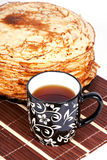 Pancakes and tea. Cup with tea and a pile of pancakes on a plate Royalty Free Stock Photography