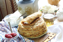 Pancakes tea in a transparent cup on a wooden table. Tea in a transparent cup and pancakes Stock Images