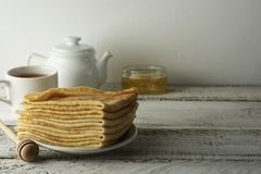 Pancakes. Thin pancakes. Russian bliny. Healthy tasty breakfast - pancakes, a cup of tea and honey. Copy space stock photography