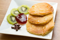 Pancakes topped with honey With kiwi jam and chocolate. Royalty Free Stock Images