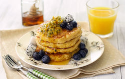 Pancakes with tropical fruits. A stack of tofu pancakes served with blueberries, tropical fruits, honey and a glass of orange juice Royalty Free Stock Photography