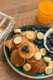 Pancakes with blueberries, banana and fresh orange juice Royalty Free Stock Photography