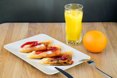 Pancakes under syrup with juice Royalty Free Stock Photography