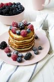 Pancakes with various berries on table, side view. stock images