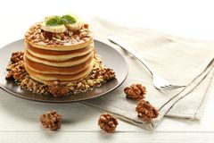 Pancakes with walnuts and bananas. Tasty pancakes with walnuts and bananas on white wooden plate Stock Photography