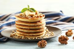 Pancakes with walnuts and bananas. Tasty pancakes with walnuts and bananas on wooden plate Royalty Free Stock Images