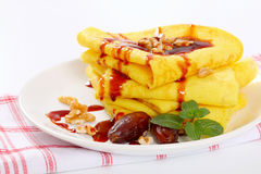 Pancakes with walnuts, dates and chocolate topping Stock Photography