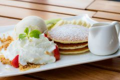 Pancakes with Whipped Cream Strawberry Banana Kiwi Syrup in wooden table top dish stock images