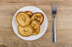 Pancakes in white plate and fork on wooden table Stock Images