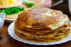Pancakes on a white plate, green onions and sour cream on the table side view royalty free stock image