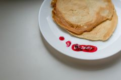 Pancakes with jam. Pancakes on a white plate with jam royalty free stock images
