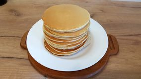 Pancakes on the white plate. Many pancakes are stacked. stock image