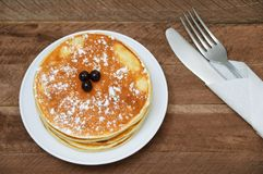 Pancakes on a white plate on wooden board royalty free stock photo