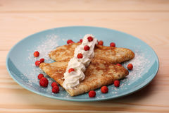 Pancakes with wild strawberries  and cream on blue plate Royalty Free Stock Photography