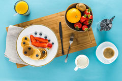 Pancakes With Berries On Kitchen Desk With Coffee And Orange Juice