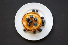 Pancakes With Blueberries And Honey On White Plate On Dark Wooden Background, Top View. Flat Lay Stock Images