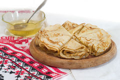 Pancakes on a wooden plate. And towel with a pattern Stock Image