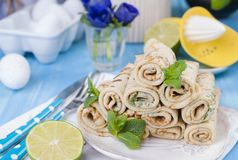 Pancakes wrapped in rum with mint on a blue background. Bright colors. stock photo