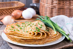 Pancakes with young green onions on a wooden background Stock Image