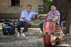 PANCEVO, SERBIA - AUGUST 1, 2015: Two Serbian musicians one accordeonist, one contrabassist having a break before a performance Stock Photos