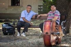PANCEVO, SERBIEN - 1. AUGUST 2015: Zwei serbische Musiker ein accordeonist, ein contrabassist, das einen Bruch vor einer Leistung Stockfotos