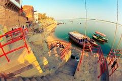 Panchaganga Ghat of Ganges River in Varanasi. Indian men reparing their boats on Panchaganga Ghat of Ganges River. Varanasi, Uttar Pradesh, India royalty free stock image