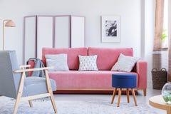 Panchetto blu accanto allo strato rosa nello spirito luminoso dell'interno del salone Immagini Stock Libere da Diritti