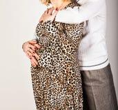 Pancia commovente della donna incinta della mano maschio, su bianco fotografia stock