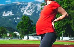 Pancia del primo piano della donna incinta sullo stadio di sport Immagini Stock Libere da Diritti