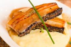 Pancia di carne di maiale sopra la polenta Fotografie Stock Libere da Diritti