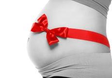 Pancia di una donna incinta legata con un arco rosso Fotografie Stock Libere da Diritti
