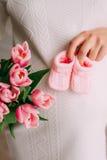 Pancia di una ragazza incinta e dei tulipani in mani Fotografie Stock