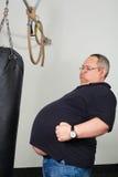 Pancia grassa della partita dell'uomo con un punching ball immagine stock libera da diritti