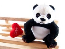Panda doll on the handmade wooden chair, feeling fall in love concept Royalty Free Stock Photos