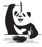Panda eating bamboo. A panda eats bamboo branches sticks Royalty Free Stock Image