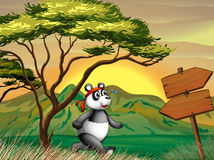 A panda following the wooden arrowboard Stock Photography