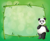 A panda beside a frame made of bamboo Stock Image