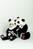 Panda love3. Child wearing a panda costume holding a little baby panda Stock Photo