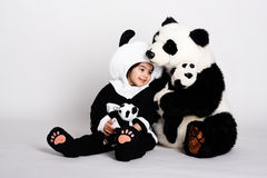 Panda love4. Child wearing a panda costume holding a little baby panda Royalty Free Stock Photography