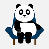 Panda sitting on the sofa and old the remote in hand for watching television. Royalty Free Stock Photo