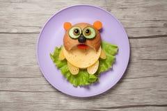 Panda som göras av bröd, ost och grönsaker på plattan och skrivbordet Arkivbild
