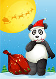 A panda wearing Santa's hat while eating a cane lollipop Stock Photography