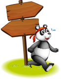 A panda beside the wooden arrowboards Royalty Free Stock Image
