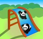Pandas playing on a slide Royalty Free Stock Photo