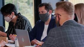Pandemic lifestyle. Serious young Caucasian businessman speaks to coworkers at meeting wearing black COVID-19 face mask