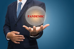 Pandemic. A man with a ball on his hand with the text pandemic Stock Photo