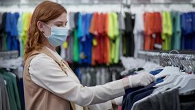 Pandemic shopping, pretty young woman buyer in medical mask and gloves chooses new clothes after quarantine cancellation