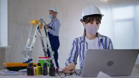 pandemic work, woman designer wearing protective helmet and face mask takes color scheme and looks at camera background