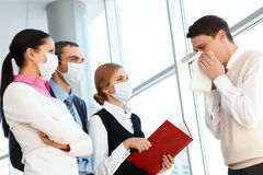 During pandemy. Group of co-workers in protective masks looking at sneezing man Royalty Free Stock Photo