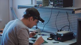 Pandown De ingenieur soldeert een elektronische component op elektrische raad stock video